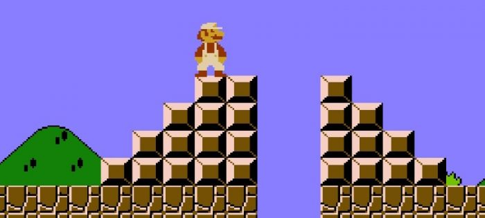 Mario stands on top of one stairway. There is a pit he needs to jump over to get to the other side alive.