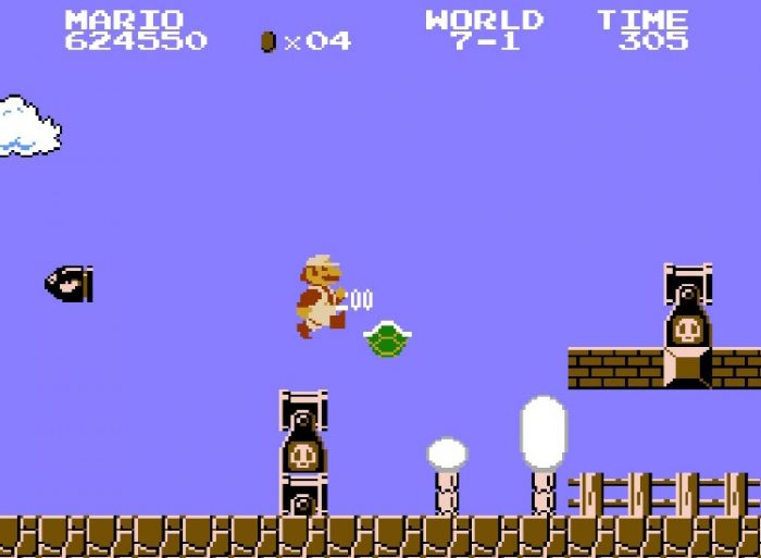 Super Mario kicks a turtle shell. Breakable bricks are nearby. Mario can go for them, but Bullet Bill cannons could fire at any moment.