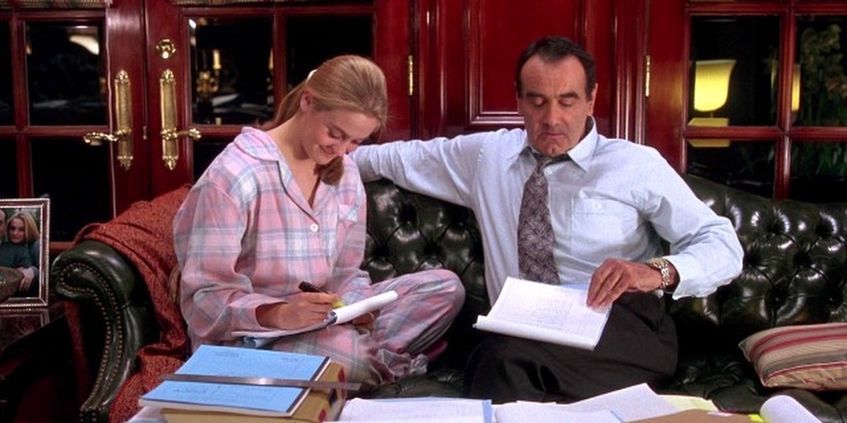 Cher and her dad sitting on a couch working on paperwork together looking down