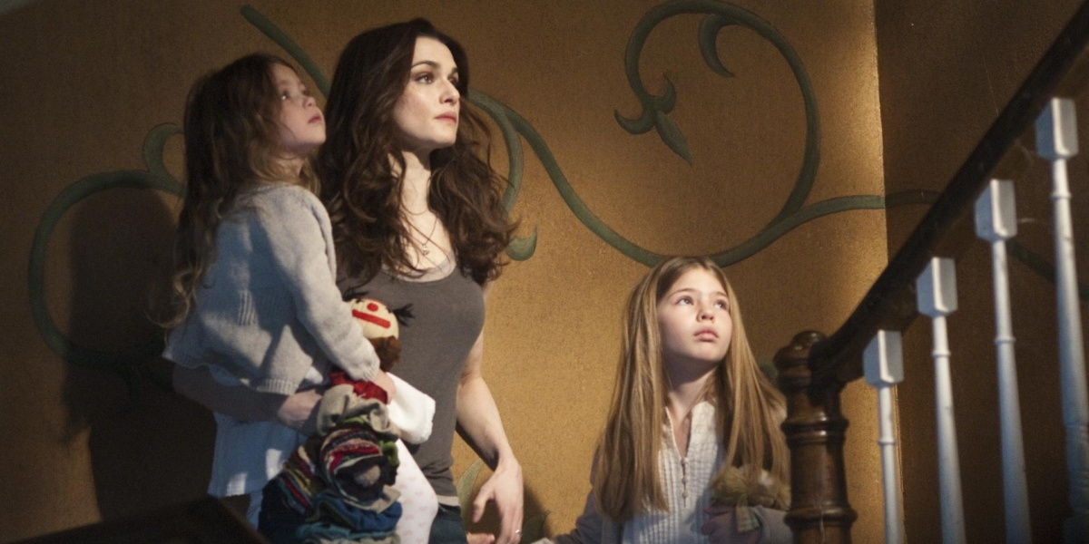 Rachel Weisz with her onscreen daughters on a staircase, yellow wall with a twisting vine painted on, all three girls with sad but accepting gazes as the girls look up and Weisz stares straight ahead