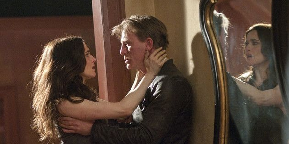 Daniel Craig and Rachel Weisz as their characters in Dream House, holding onto one another, intense expressions of pain on their faces, with their reflections in a mirror to Craig's left