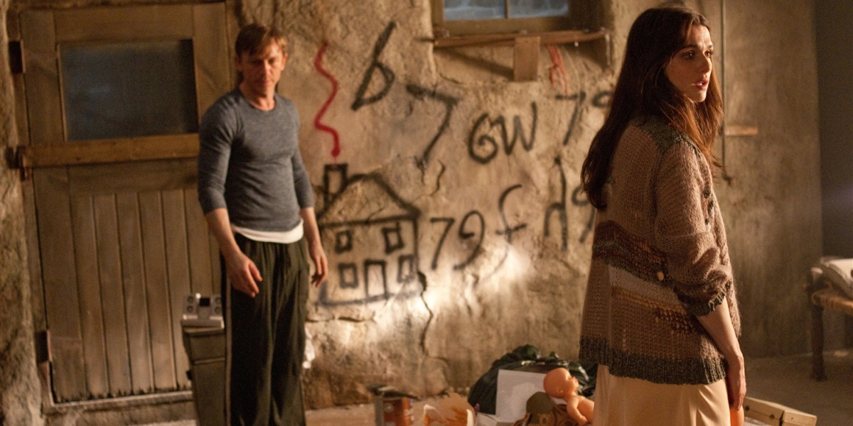 Rachel Weisz stares at something behind her apprehensively, while Craig stares at the ground, strange writing on the wall behind them in Dream House