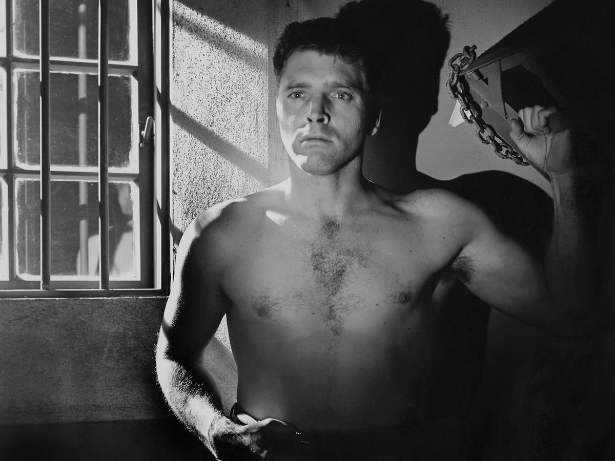 Joe Collins (Burt Lancaster) standing shirtless in a jail cell