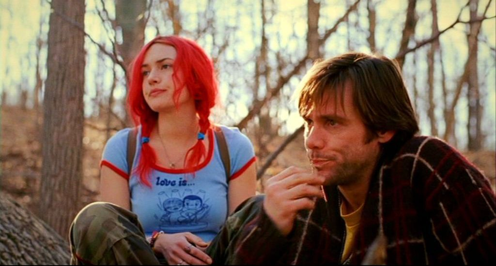Clementine and Joel sit outside in a wooded area looking glum