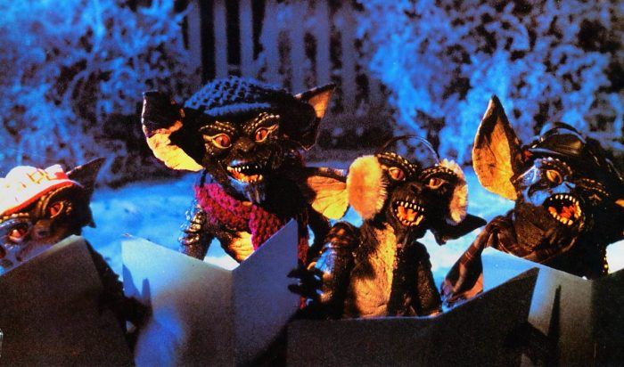 Stripe and his fellow evil Gremlins ssing Christmas carols outside Mrs. Deagel's house