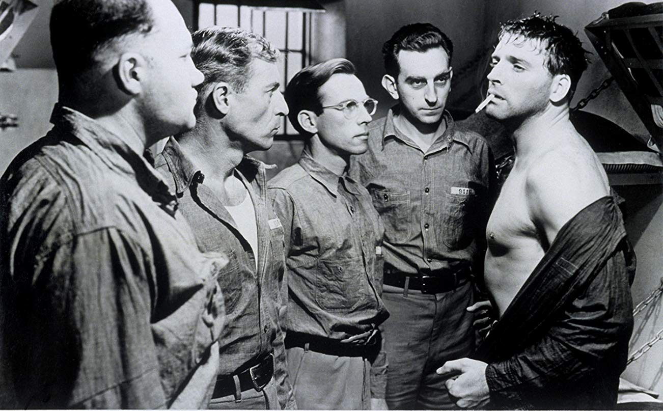 Inmates in a jail cell stare down Joe Collins (Burt Lancaster)