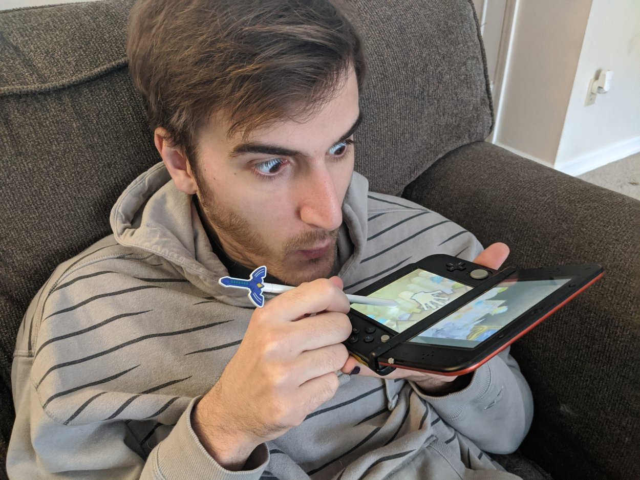 Sean, the author of the article blowing into his Nintendo DS to demonstrate the pan pipe playing mechanic in The Legend of Zelda: Spirit Tracks.
