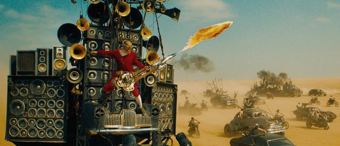 The Doof Warrior plays his fire guitar surrounded by lots of cars in the desert of Fury Road