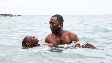 A man helps a boy swim in the ocean