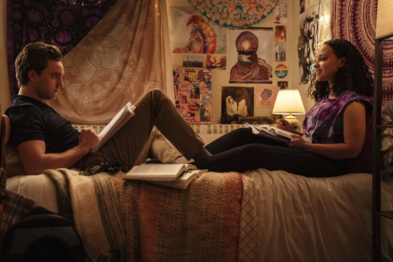 Brendan and Chloe sit on Chloe's bed looking at each other and surrounded by school books