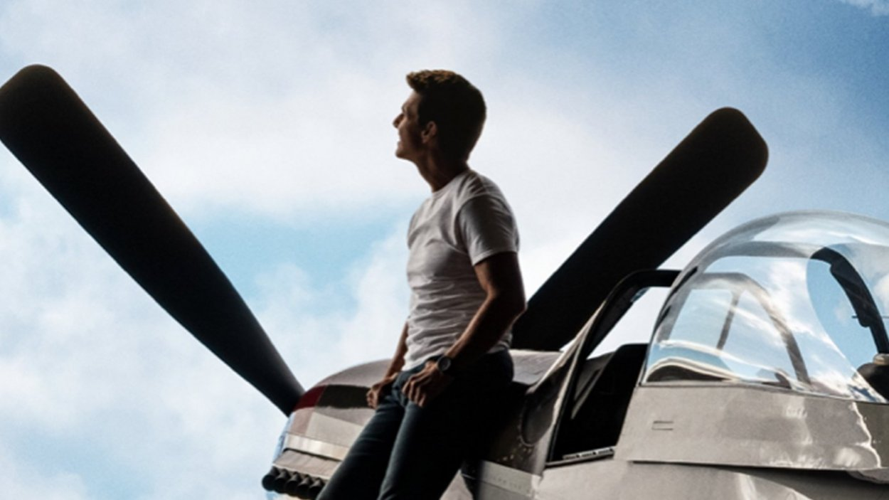 Maverick looks at the sky while leaning on his fighter jet