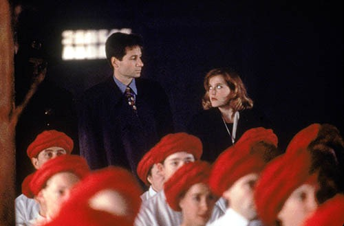 Mulder and Scully look skeptically at one another as they watch from the back of a church full of vergetarions wearing blood red turbins.