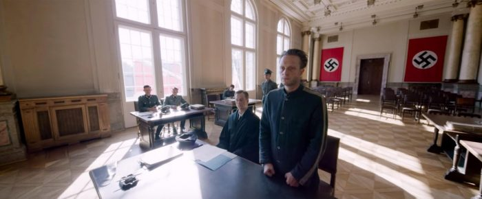 Franz stands at a table with his lawyer surrounded by Nazi insignia