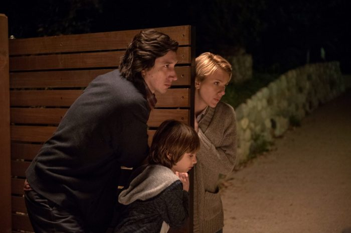 Adam Driver and Scarlett Johansson close a gate with their son at night