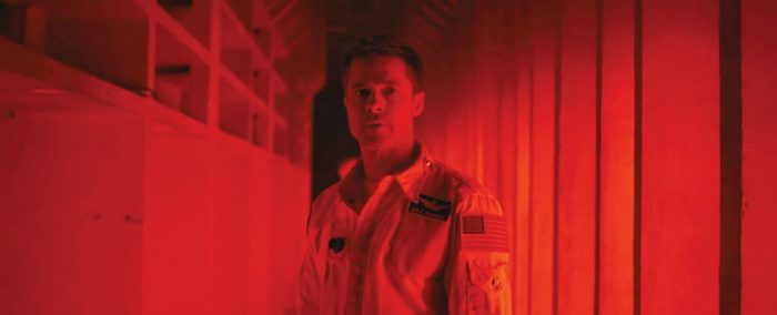 Brad Pitt stands in a red hallway looking at something unseen