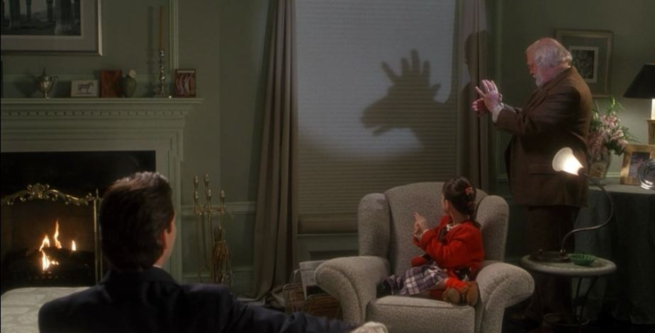 Santa makes reindeer shadow puppets on the wall