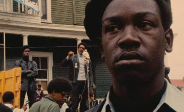 A Black Panther stands guard as a man speaks in the background to a crowd