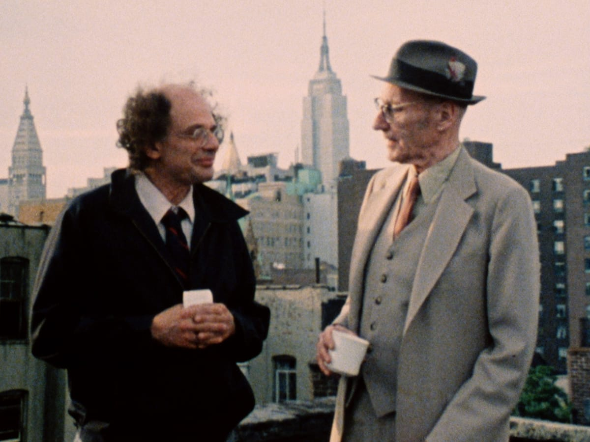 Ginsberg and Burroughs talk on a roof with the New York City Skyline behind them
