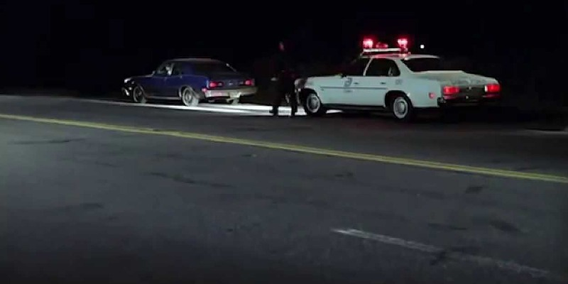 Wide shot of a road at night in foreground; in background, a car pulled over by a police car behind it, the officer standing between the two vehicles in the light of the police car's headlights.