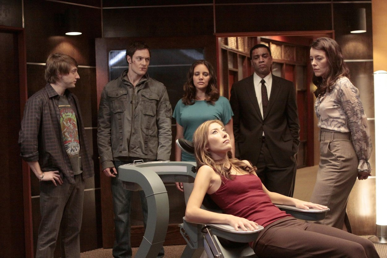 Sierra lies back in the chair, with Topher, Paul, November, Boyd, and Adelle gathered round her