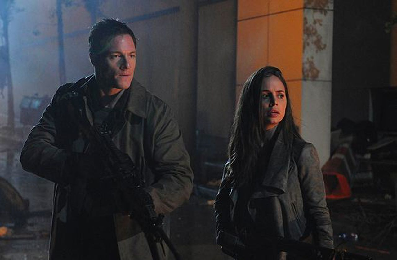 Paul and Echo on a dark city street, holding big guns