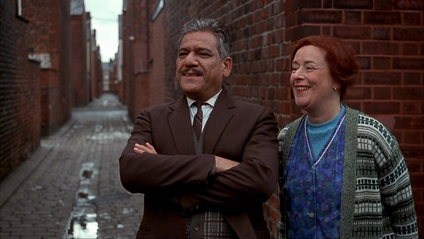 George and Ella look on into the street, smiling proudly