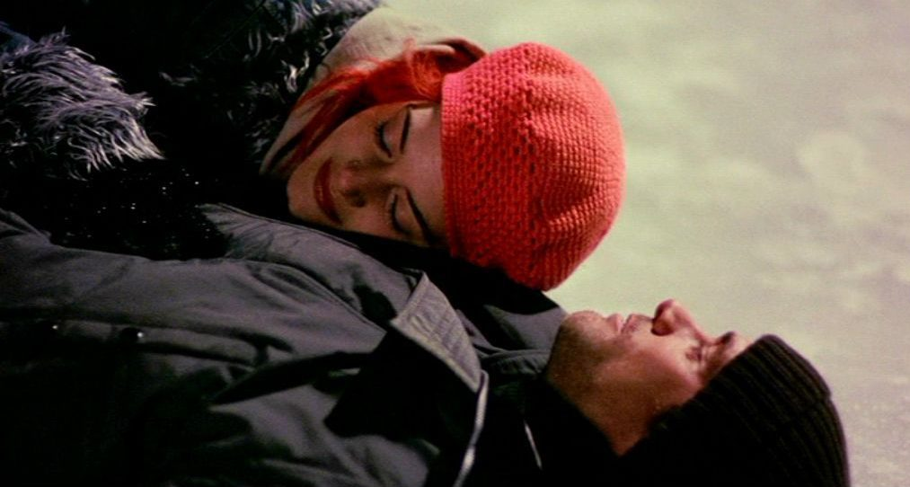 Clementine lays in Joels arms on the frozen river