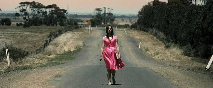 Lola Stone walks in her pink prom dress down a road holding a knife in her right hand.