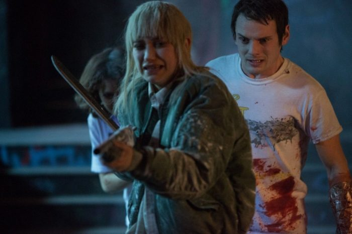 Amber brandishes a shotgun with a distressed look on her face while Pat and Sam hide behind her.
