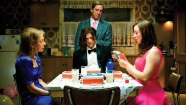 Brent sits dazed at the kitchen table, flanked by Lola and an old woman in a blue dress, while Daddy stands behind him.