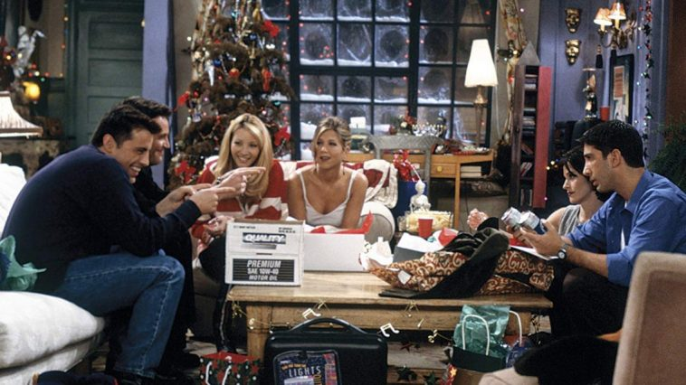 The friends open presents around the table