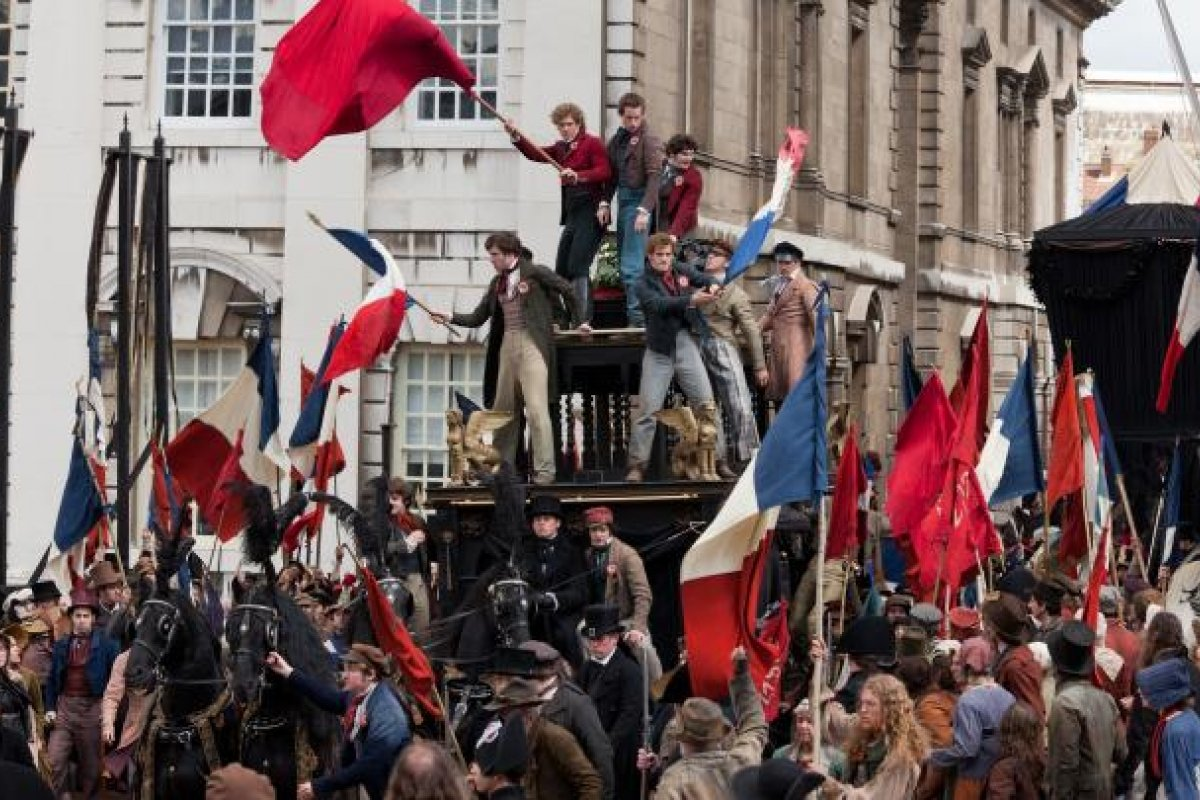 The students standing on a carriage, wave flags at the barricade in Paris