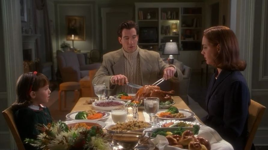 Thanksgiving dinner in A Miracle on 34th St, Susan, Bryan and Dorey sit around a table with a lot of food