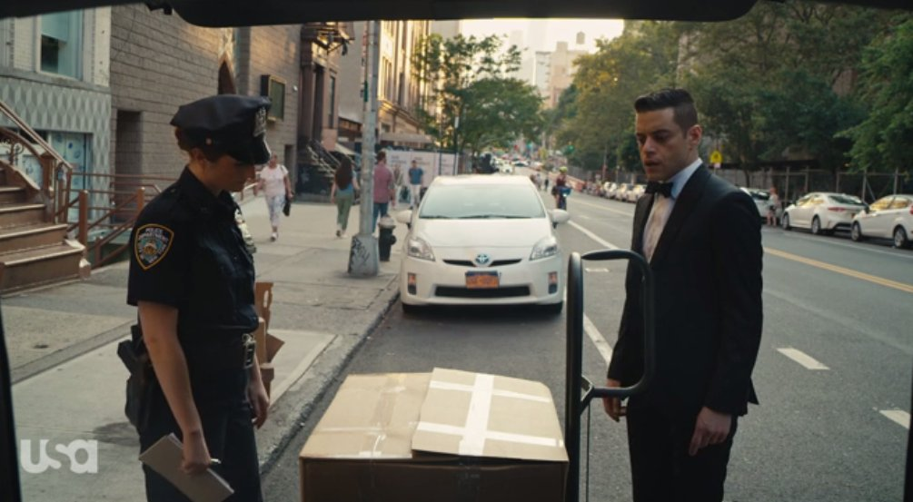 Dom as a cop confronts Elliot over a large box