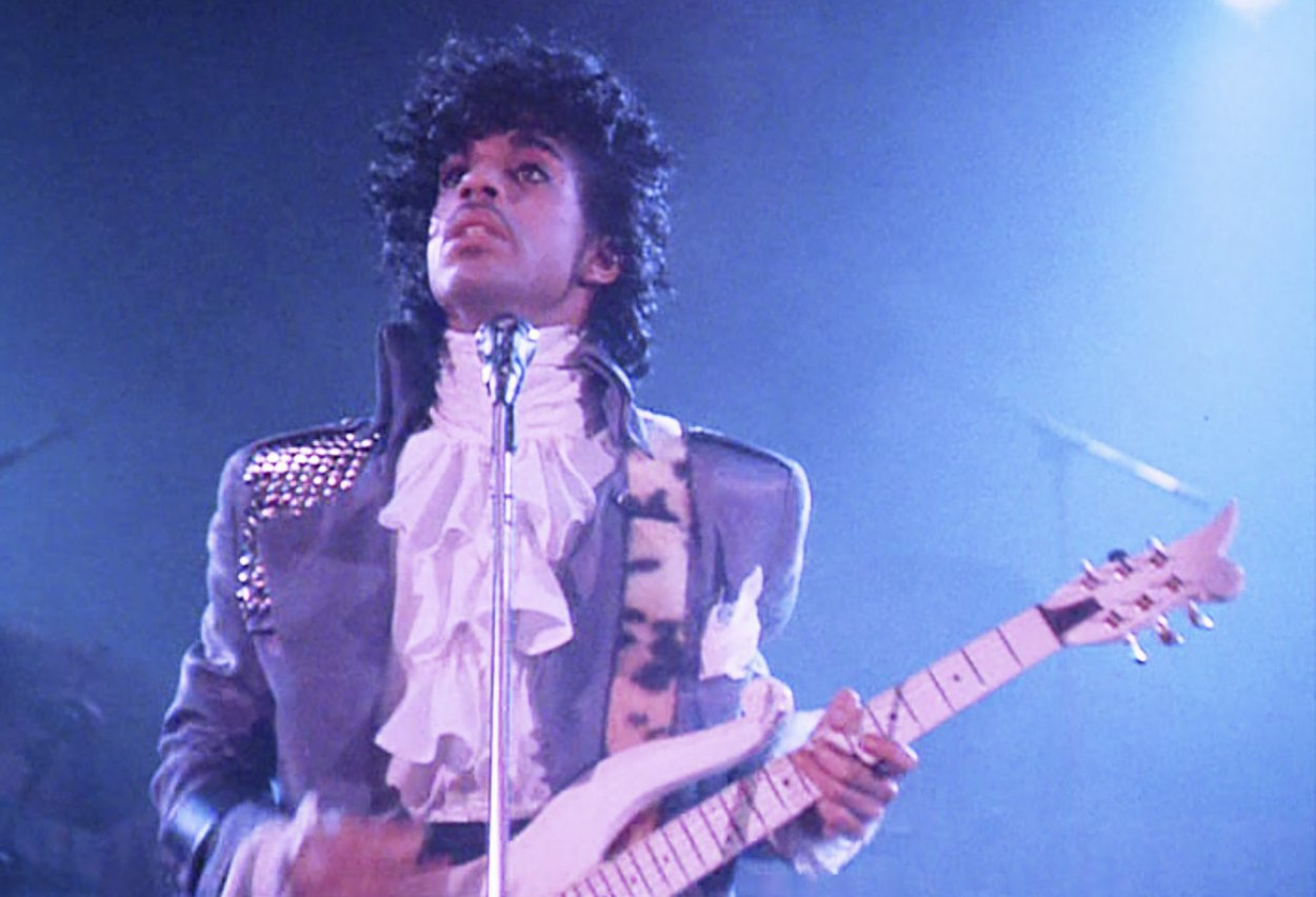 Classic image of Prince holding his guitar during Purple Rain performance