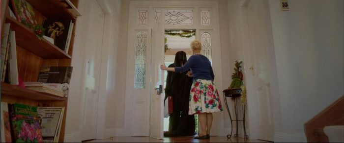 Diane invites a cloaked man into her home in Red Christmas