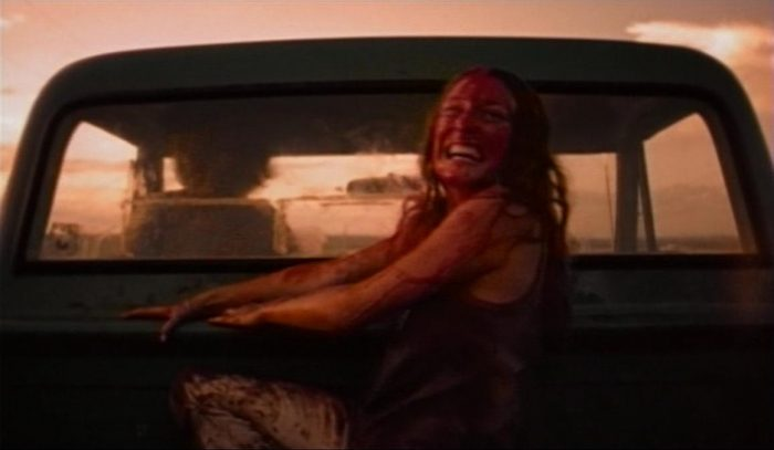 Sally hitching a ride away from a disappointed Leatherface at the end of The Texas Chain Saw Massacre.