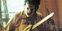 Leatherface, chainsaw in hand, getting down to work.