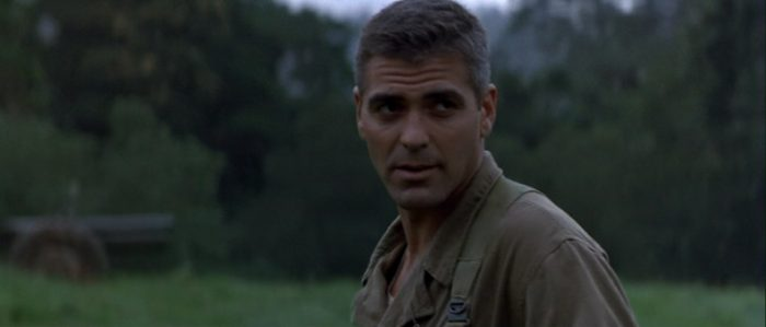 George Clooney stands in an empty field