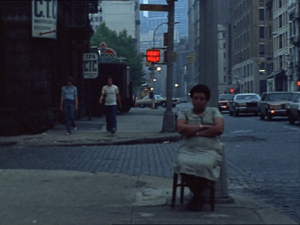 A woman sits with her hands folded on a street corner with two men walking in the background