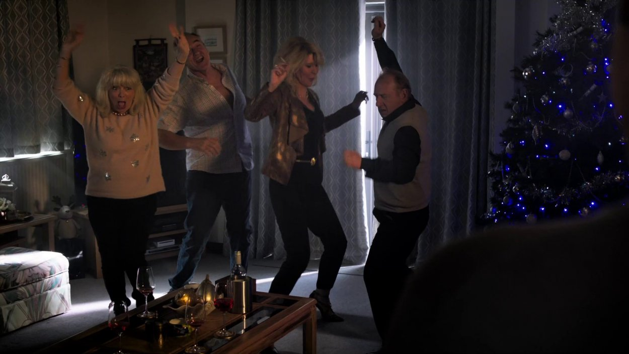 Pam, Mick, Dawn, and Pete dance around a dark living room as they get stoned