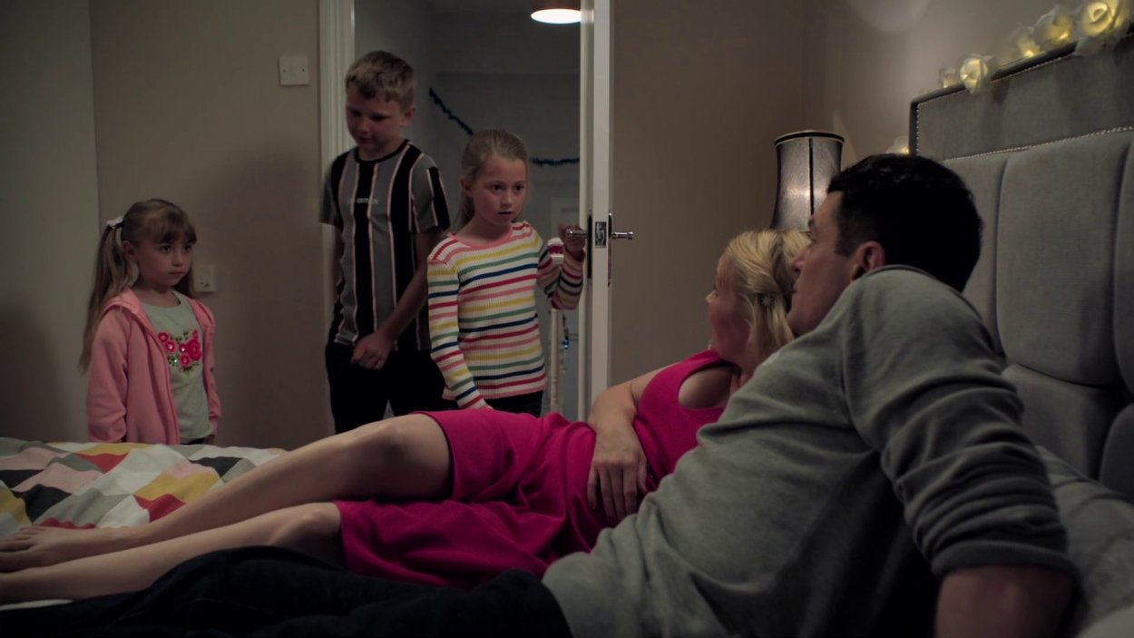 Gavin and Stacey kiss on the bed as their three children stand in the doorway interrupting them