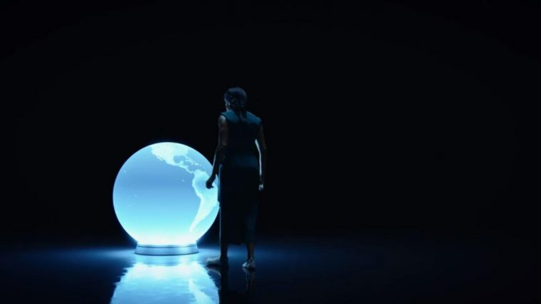 Angela approaches a blue lit model of the earth in a darkened room