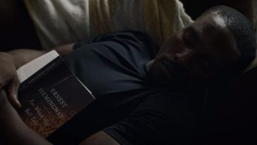 Cal sleeps on the sofa with the book For Whom the Bell Tolls