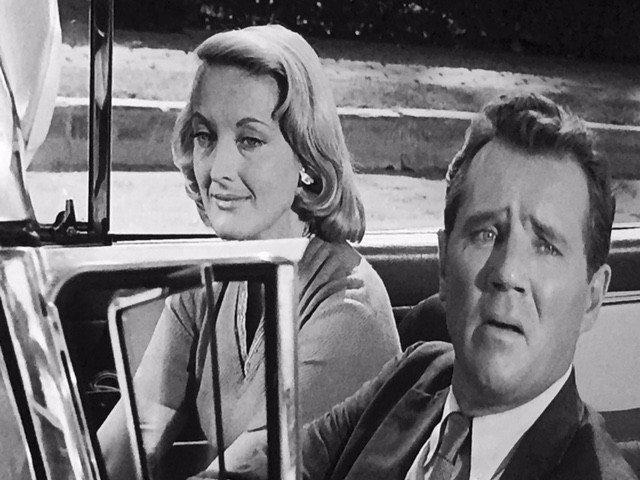 "Arthur/Gerry looks confused in his car with his ""wife"" Nora"