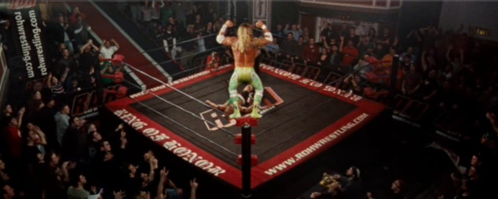Randy stands dominantly on the top turnbuckle, posing over the ring