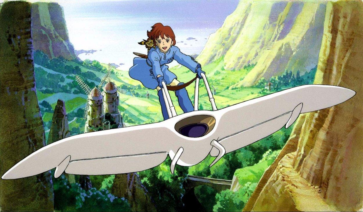 Nausicaä flies through a canyon , standing on her glider