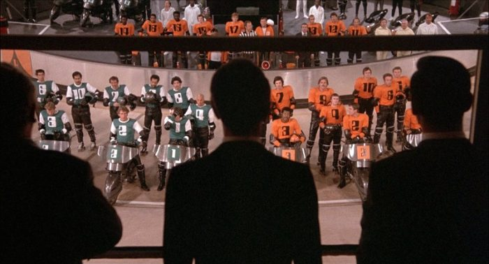 Two rollerball teams stand on the rink in front of corporate chairmen