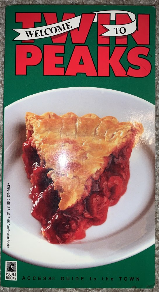 """Welcome To"" is on a white scroll wrapped around the red letters of ""Twin Peaks"", while the comically unprofessional image of a cherry pie slice on a white plate is on top of a flat green background."