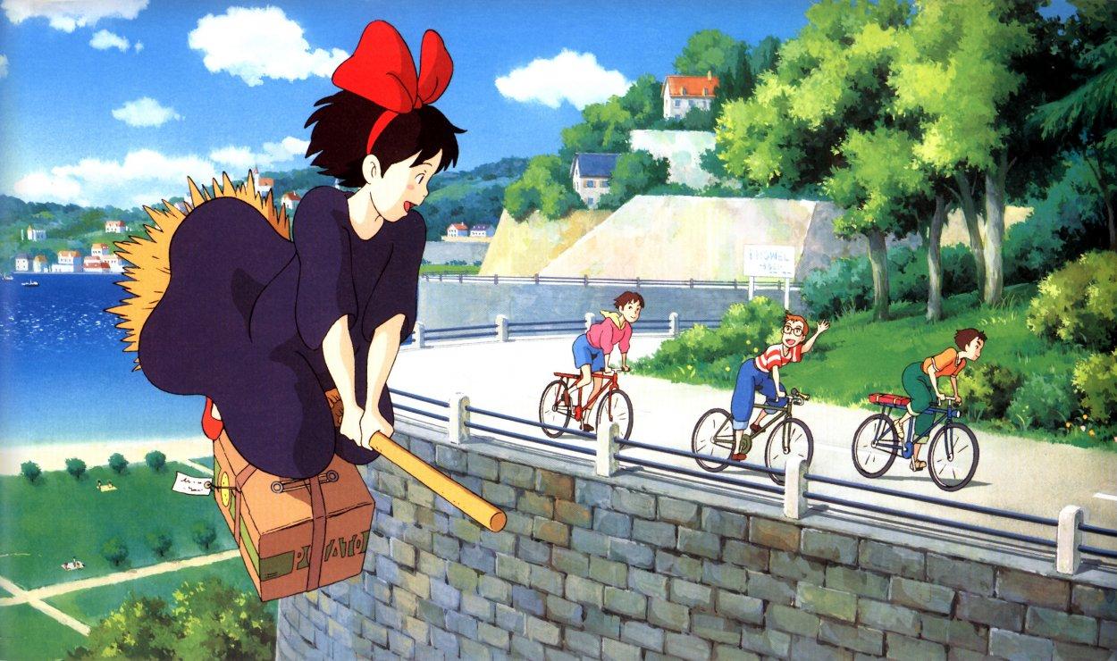 Kiki flies on her broom alongside Tombo and his friends on bikes